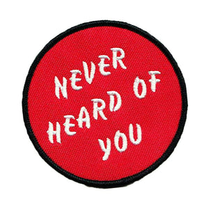 "Red ""Never Heard of You"" embroidered iron-on patch. Circular patch with ""Never Heard of You"" text in three lines diagonally."