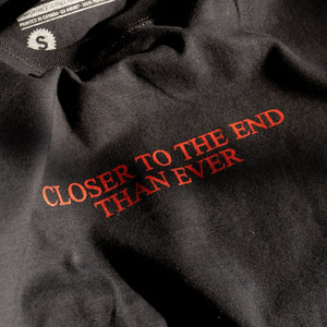 "Detail photo of our original ""Closer"" t-shirt.  T-shirt is black with red chest print that reads ""CLOSER TO THE END THAN EVER""..  Based off of posters put up in our neighbourhood warning people about No Fun®."