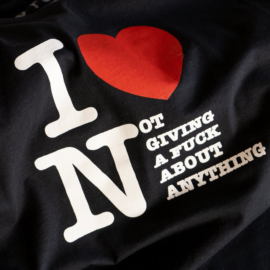 "Black t-shirt with big chest print that reads ""I heart Not Giving a Fu** About Anything"". Design references the classic ""I Heart NY"" tee."