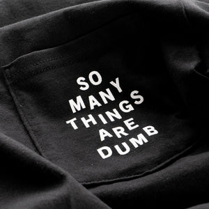 "Detail of the original NO FUN® ""So many things are dumb"" pocket tee. This closeup image showcases the front pocket detail, and the white text that reads ""So Many Things Are Dumb""."