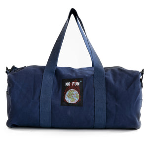 "The ""Life Is Hell"" duffle from No Fun Press. Navy duffle bag, showing the side that has a woven tag sewn on. The tag depicts a burning globe.."