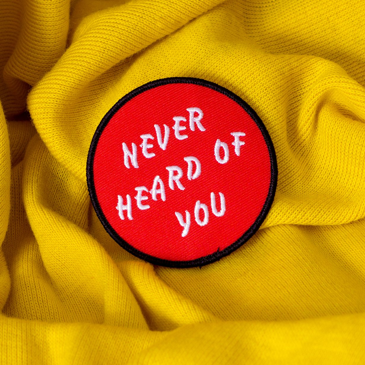 "The No Fun Press original ""Never Heard of You"" embroidered iron-on patch, on yellow fabric."