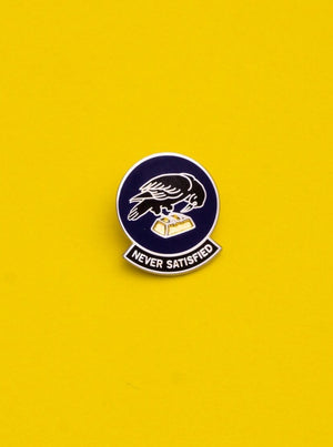 "No Fun Press - ""Never Satisfied"" raven enamel lapel pin on a yellow background."