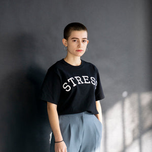 "Photo of a model wearing the original NO FUN® ""STRESS"" t-shirt. Shirt is black and features large white collegiate style text that reads ""STRESS"" across the front in an arc shape."