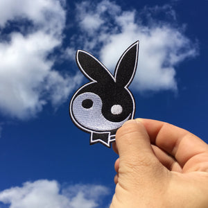 "No Fun Press - original ""yin yang bunny"" embroidered iron-on patch held up against the sky."