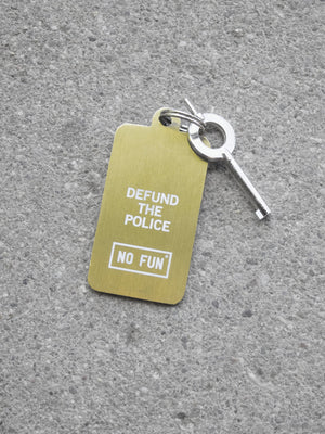 "Photo of the backside of our authentic ""ACAB"" keychain.  The phrase ""Defund the Police"" is engraved into the brass tag and filled with white enamel.  The ""NO FUN®"" logo is below the phrase, also engraved and filled with white enamel.  The authentic handcuff key is attached to the keychain."