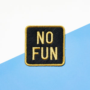 "Black and gold ""No Fun®"" logo patch on a white and blue background."