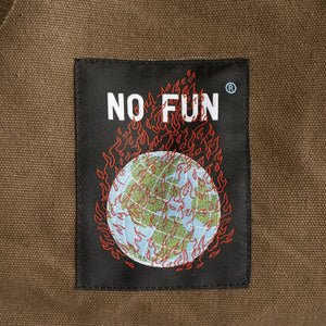 "A detail of the ""Life is Hell"" duffle bag, focusing on the embroidered label of a burning globe."