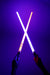 "A photo of two hands holding two novelty light up swords.  The light from the swords is illuminating the background in a purple colour.  The sword in the left hand is red , while the right hand is holding blue.  They are crossed in the middle and ""NO FUN®"" logos are visible to the camera."