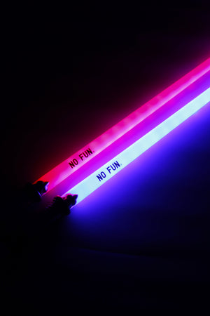 "A close up photo of two light up swords showcasing the ""NO FUN®"" logos close to the handle.  The novelty sword on the left is illuminating the dark background with red light, while the novelty sword on the right is illuminating the dark background with blue light."