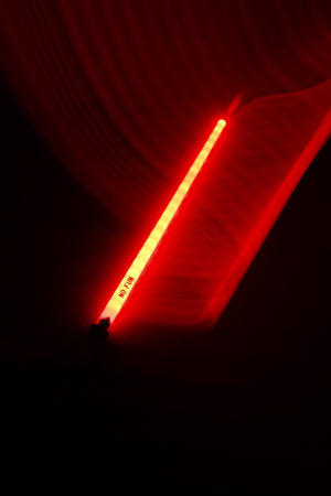 "A photo of a red novelty sword illuminating a dark background.  There is a light trail flowing from the sword to the top of the image, showcasing the colour.  The ""NO FUN®"" logo near the handle is visible to the camera."