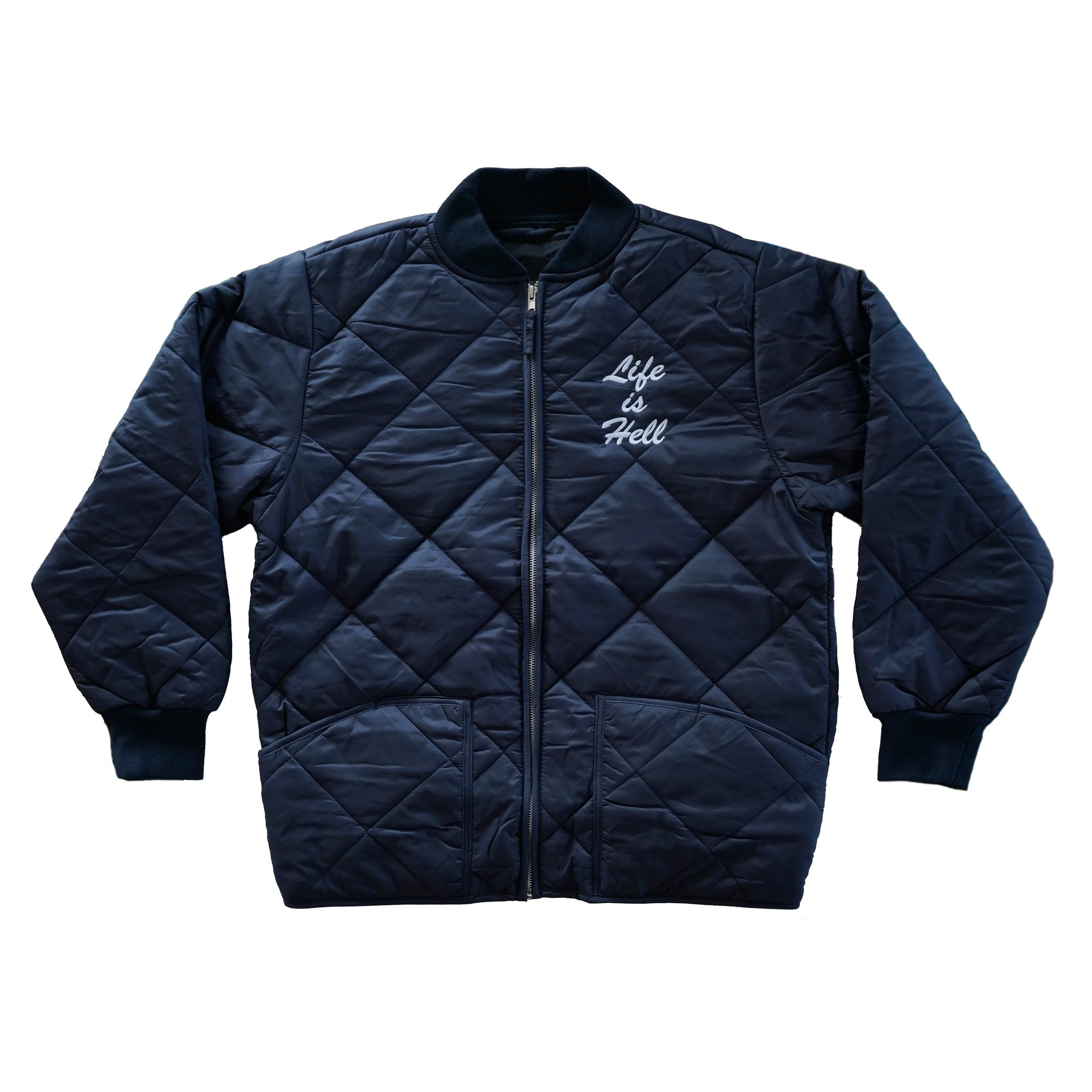 "Product photo of the official No Fun® ""Life Is Hell"" Quilted Bomber Jacket in the navy colourway.  The product is photographed on a white background, with the sleeves of the jacket folded over.  The jacket features the text ""Life Is Hell"" embroidered on the front of the jacket in white.  The jacket also features a zipper in the front, and full quilting on the entire outer shell."