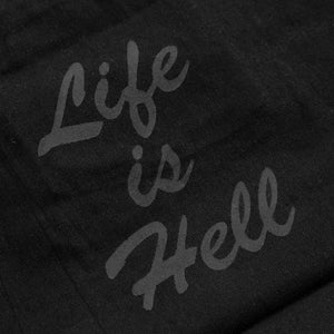 "Detail of the ""Life is Hell"" text on a zippered tote bag."