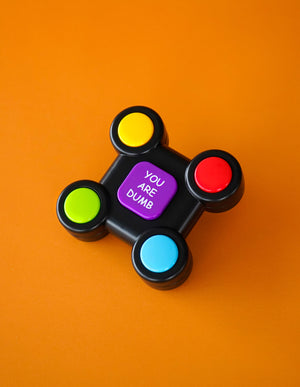 "Photo of the ""No Fun®"", ""You are Dumb"" Electronic memory game. The game is black, with four different coloured buttons than can be found in each corner. The buttons are yellow, red, green, and blue. In the center of the game there is a larger square button that is purple, with the phrase ""YOU ARE DUMB"" printed in white text. The memory game is photographed against an orange background."