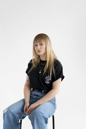 "Photo of a female model wearing the original NO FUN® ""So Many Things Are Dumb"" Pocket tee, designed and printed in Toronto. T-shirt features front pocket and white text that reads ""SO MANY THINGS ARE DUMB""."