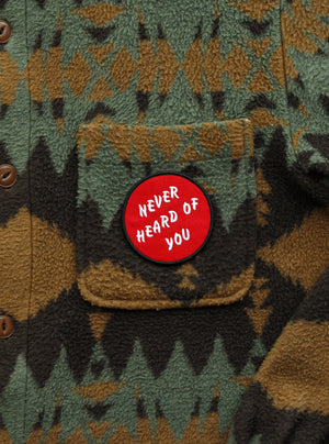 "Red ""Never Heard of You"" embroidered iron-on patch. Circular patch with ""Never Heard of You"" text in three lines diagonally.  Photo shows the patch adhered to a fleece jacket."