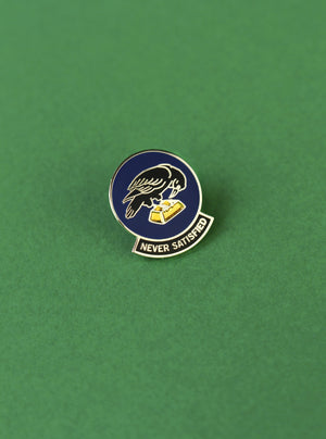 """Never Satisfied"" navy, silver, and gold raven enamel lapel pin from No Fun®.  Pin is photographed on a green background"