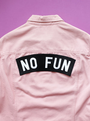 "Original ""No Fun"" XL size rocker embroidered iron-on back patch.  Patch is adhered on a pink denim jacket, set against a purple background."