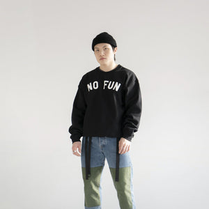 "Photo of a male model wearing the original ""NO FUN®"" logo crewneck sweater. The sweater is black and features large white text that reads ""NO FUN®""."