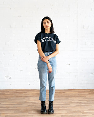 "Photo of a female model wearing the original NO FUN® ""STRESS"" t-shirt. Shirt is black and features large white collegiate style text that reads ""STRESS"" across the front in an arc shape."