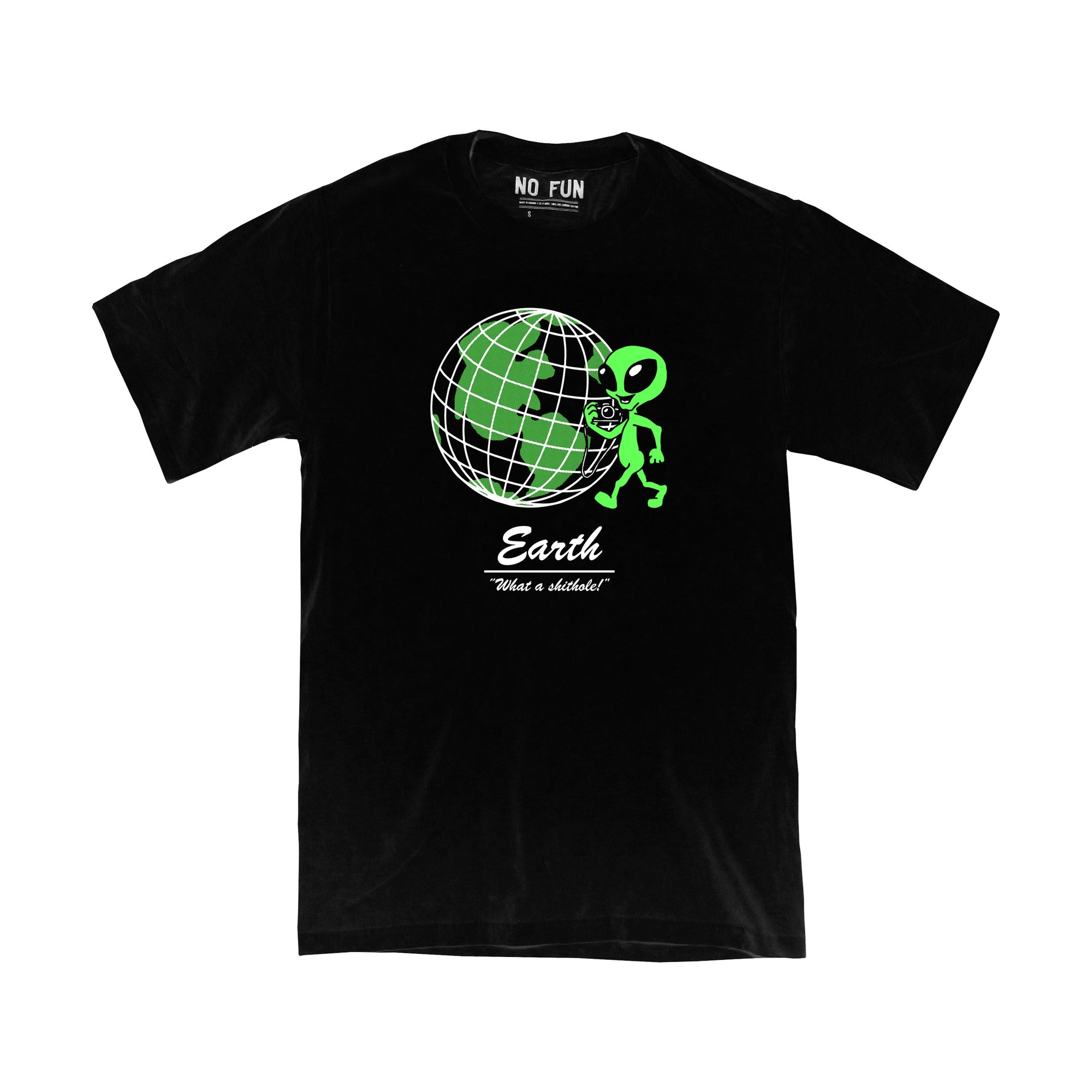 "Photo of the original ""Tourist"" T-shirt by NO FUN®.  T-shirt is black and features an image of the planet earth in green and white, alongside an alien holding a camera in green.  The text underneath the graphic reads ""Earth 'What a shithole!""."