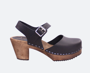 Highwood clog in Black with Brown Base by Lotta from Stockholm, Classic Mary Jane style clog with black leather, closed toe and buckle ankle strap. Brown wooden base with 7cm (2.75 inch) heel and 2cm (0.75 inch) platform.