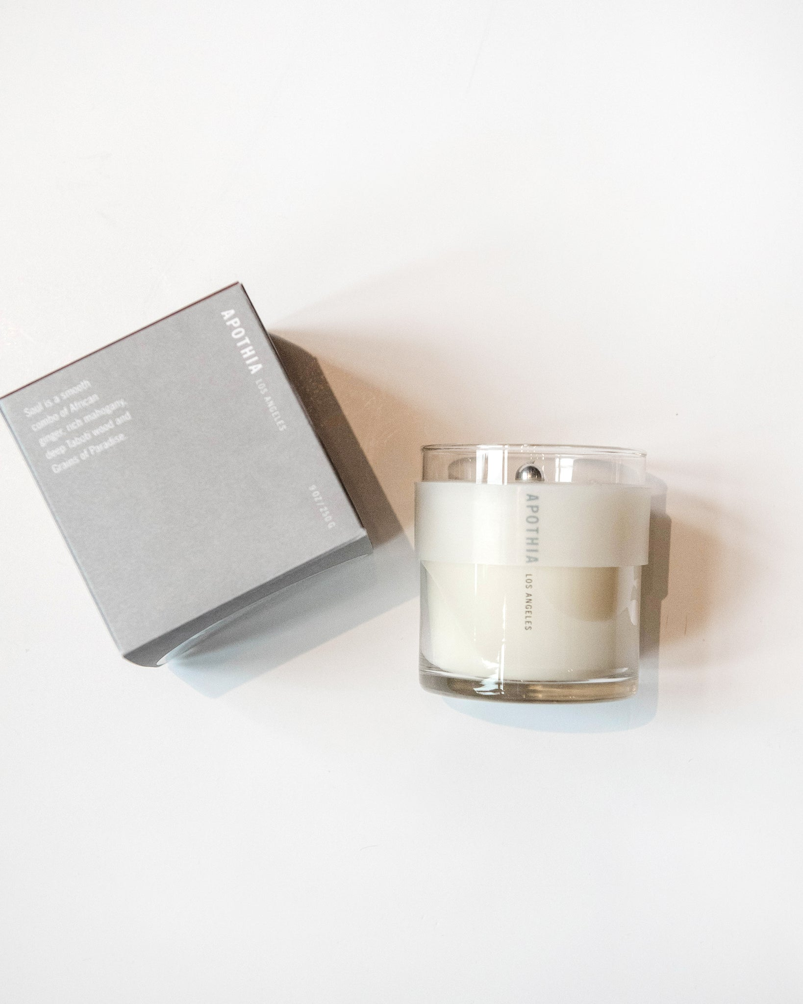 "Sleek white candle in a 9oz jar combines notes of African ginger, rich mahogany, deep taboti wood, and grains of paradise. Also includes a patented, heat protected ""halo"" band around top of glass for ease of moving. 60 hour burn time."