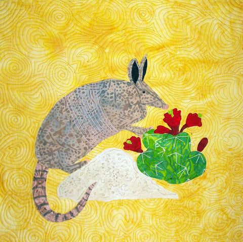 Armadillo on a rock eating a red flowered cactus