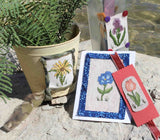 Buy Antique Flower Cross Stitch Patterns Collection includes a blue morning glory card, peach tulip bookmark, yellow sunflower decorated can, and purple iris on glass patterns.