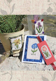 Buy Antique Flower Cross Stitch Collection includes a blue morning glory card, peach tulip bookmark, yellow sunflower decorated can, and purple iris on glass patterns.