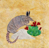 The Armadillo southwest desert quilt block completed photo features an armadillo on a rock near a green claret cactus with red blooms on a yellow background.  Buy Purchase for Sale Raspberry Lane Crafts.