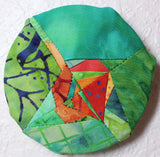 Aspen Leaf Hanger sewing pattern decoration completed hanging on wall features a leaf in orange batik fabrics and background of green batik fabrics.  Found in Leaf Hanger Pattern at Raspberry Lane Crafts.