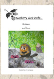 Raspberry Lane Crafts The Beaver digital download is a quilt block pattern of a beaver on a muddy bank with a grassy background.
