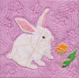 Rabbit block features a white bunny with pink ears and nose smelling a yellow and gold dandelion.  Quilted into a wallhanging for Easter or Springtime called Blooming Spring at Raspberry Lane Crafts.