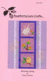 Front pink cover of Raspberry Lane Craft's Blooming Spring quilt pattern featuring six inch blocks of a white rabbit, yellow flowers, and yellow chick with leaves.