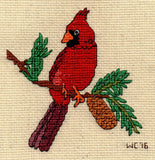 Find Red cardinal cross stitch pattern download on a brown pine branch with green pine needle clumps and light brown pine cone.