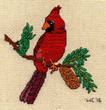 Red cardinal cross stitch on a brown pine branch with green pine needle clumps and light brown pine cone.