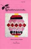 Front cover of Chinese Lantern Freedom 12 inch quilt block pattern features the Raspberry Lane Crafts logo and photo of completed pattern.  Purchase pattern here.  Designed by Wendy Christine 2018. Copyright