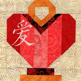 Chinese Lantern Love pattern is pictured here made of red and pink fabric in a heart shape with gold-yellow handle and base.  The Chinese symbol for love is in white.  Designed by Wendy Christine at Raspberry Lane Crafts