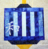 Chinese Lantern Peace quilt block pattern features blue strips in various shades with gold top and bottom.  Raspberry Lane Crafts.