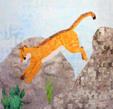 "An orange mountain lion leaps into green grassy areas from huge gray-brown textured rocks in ""Cougar Jumping"" quilt block pattern by Wendy Christine at Raspberry Lane Crafts."