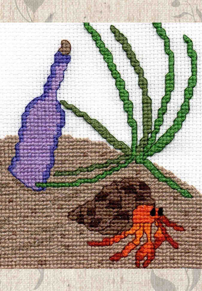 Buy ocean seashore beach cross stitch patterns at Raspberry Lane Crafts.  The Crab and the Bottle on sand is stitched in this cute cross stitch.