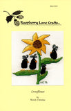 Crowflower cross stitch pictures four cute teardrop black crows on the leaves of a gold sunflower.  Design by Wendy Christine