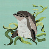 Dolphin with Kelp completed cross stitch picture features a gray dolphin with green flowing kelp on a blue background.  Raspberry Lane Crafts.  Pattern for Sale.