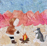 Raspberry Lane Crafts Dusk by the Fireside features a bundled up person by a campfire with a husky dog pink sunset mountains