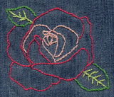 Full Rose embroidery in color on jeans features a two tone pink rose outline with green leaves.  Part of the Rose Blooms embroidery pattern download available at Raspberry Lane Crafts.