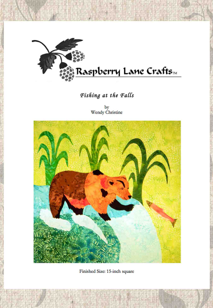 Fishing at the Falls quilt block pattern digital download cover features the finished quilt block of a grizzly bear at the top of a waterfall stream batting at a pink salmon with tall river grass in the background.  Raspberry Lane Crafts.