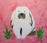 Flop eared Bunny quilt block pattern features a white droopy eared bunny with brown spots and green grass on a pink block.  Available at Raspberry Lane Crafts.