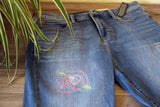 Full Rose embroidered on a pair of blue jeans.  Pattern available at www.raspberrylanecrafts.com