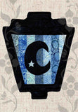 Half moon with star cut out silhouette on blue stripes gaslight lantern Halloween sewing pattern available at Raspberry Lane Crafts.